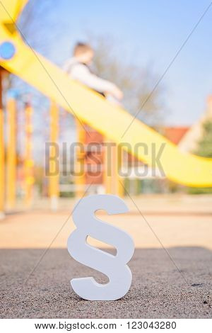 White paragraph symbol on children playground. Family law or playground accident concept.