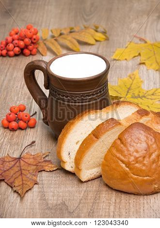 cup of milk and bread on wooden background. vertical photo.