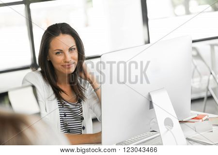 Attractive brunette woman at office desk work on computer