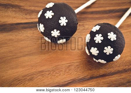 Two cakepops with snowflakes decoration on a wooden background