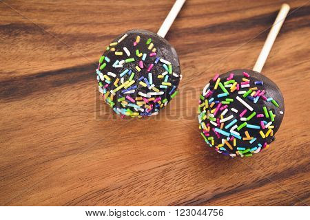 Cakepops in chocolate glaze with colored decoration on a wooden background