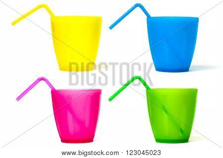 Plastic picnic glasses with drinking straws in different colors isolated on white background