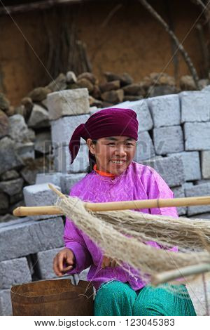 HA GIANG, VIETNAM - FEB 7, 2014: Unidentified Hmong woman making silk threads from raw material (one kind of wild tree).