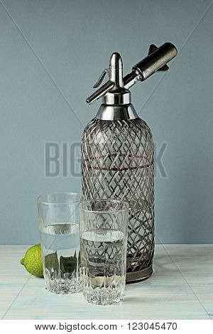 Siphon and two glasses with soda water on a gray-blue background