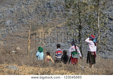 Hmong family walking home through a rocky mountain from a weekly traditional flea market.