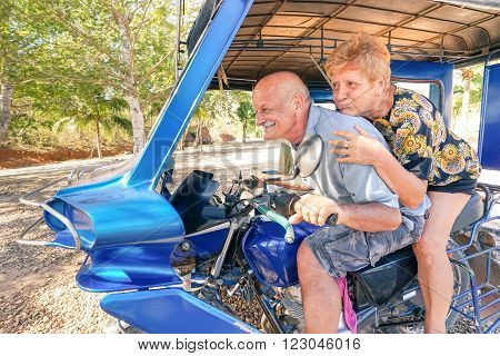 Happy senior couple having fun with tricycle in Philippines travel - Concept of active playful elderly during retirement - Everyday joy lifestyle without age limitation - Warm afternoon color tones