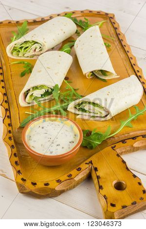 Cold wraps filled with ham and iceberg lettuce. Served with yogurt sauce on a wooden cutting board