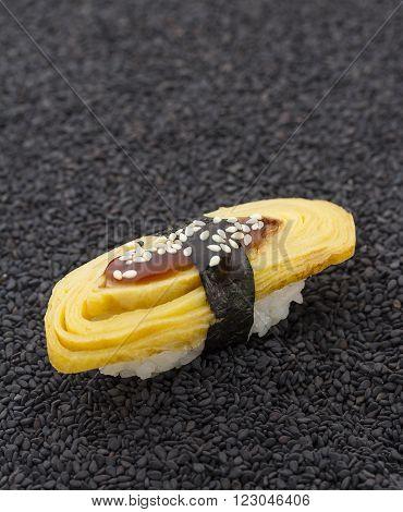 Tomago Sushi Nigiri On Black Sesame Background
