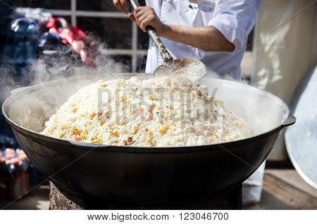 Big pot with Plov national Kazakh food on the street of Almaty during Nauryz festival in Kazakhstan