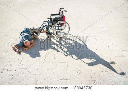 Disabled man with handicap having an accident crash with wheelchair - Disability concept with powerless unhelped person lying on the floor - Social issues with invalid guy on difficultes
