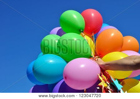 multicolored balloons in the human hand in the city festival on blue sky background