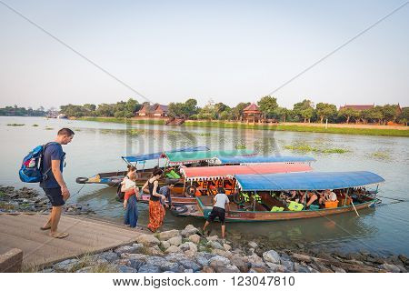 Ayutthaya, Thailand - March 16, 2016: Foreigner tourists were waiting to get in the long trail boats with colorful roof canvas from small pier of Chaopraya River, Thailand.