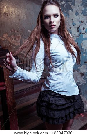 Young beautiful girl wearing school outfit in the abandon place