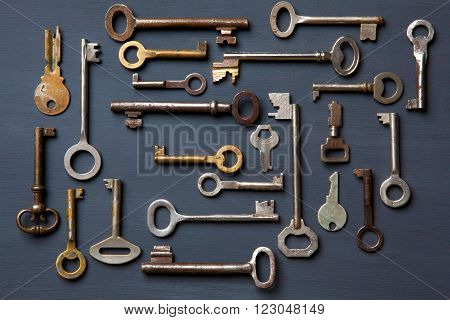 Set of old keys on a gray wooden board
