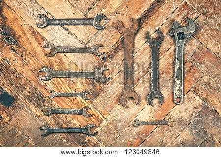 Set of old rusty wrenches on wooden floor