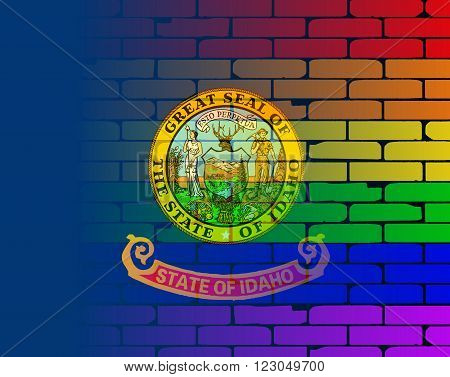 A well worn wall painted with a LGBT rainbow with the Idaho state flag