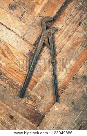Old rusty pipe wench on wooden floor