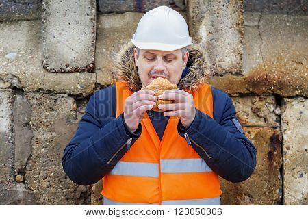 Worker eating hamburger at outdoor in winter day