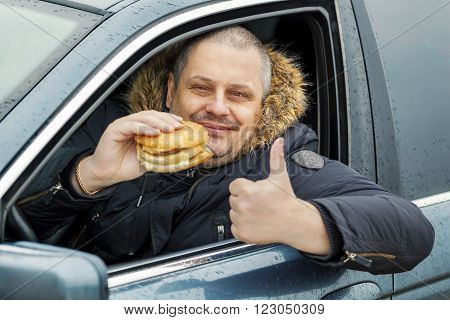 Happy man with hamburger shows thumb up in the car