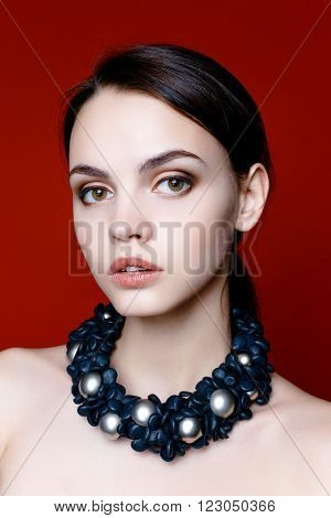 Portrait of pretty young woman with beads on red background. Beauty Woman face Portrait. Beautiful Spa model Girl with Perfect Fresh Clean Skin. Youth and Skin Care Concept.