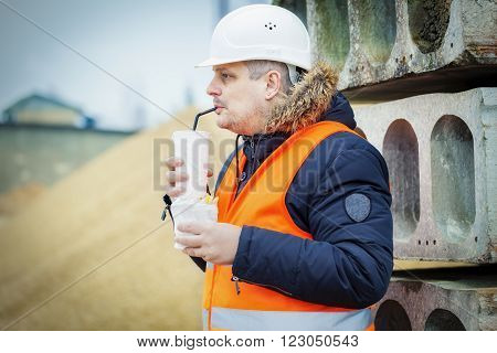 Worker drinking soda and eating french fries at construction site