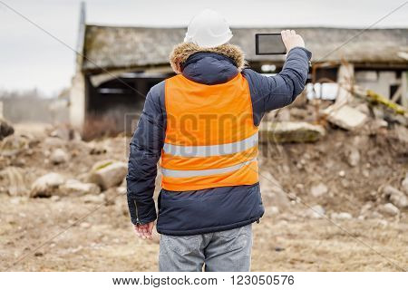 Engineer filming near to the destroyed buildings