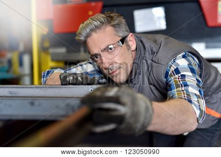 Metalworker checking piece of iron in workshop