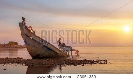 Young Couple On The Sunken Ship Is Looking On The Tropical Sunset.