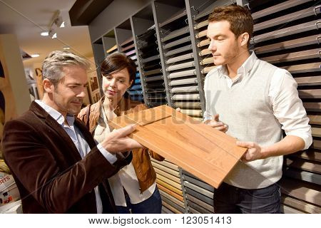 Couple with salesman in kitchen furniture store