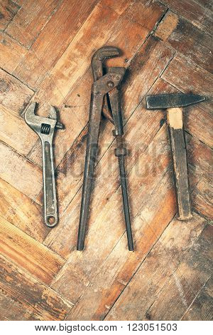 Set of old adjustable spanner pipe wrench and hammer on wooden floor