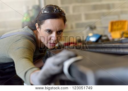 Metalworker sanding down piece of metal