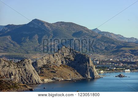 Scenic view in distance towards Sudak valley with Genoese Fortress and Palvani-Oba Mountain in front of town and Ai-Georg Mountains on background from top of Koba-Kaya Mountain Crimea Russia.