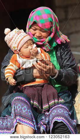 HA GIANG, VIETNAM - FEB 7, 2014: Unidentified Hmong woman holding her baby on arms in front of her house under the sunlight of spring.