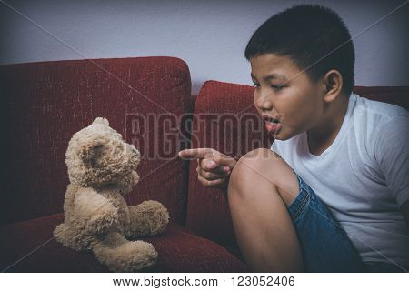 Young Asian boy scared and alone, pointing at his teddy