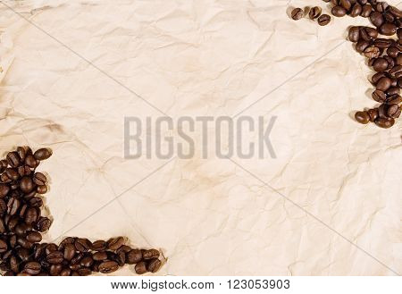 Coffee beans forming a frame on old crumpled paper (as a background with copy space for your text)