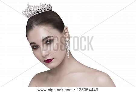 Glamorous brunette with bare shoulders crown on his head looking at the camera head bowed