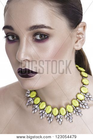 White girl with dark make-up, with aubergine lips looking at the camera. Calle on the neck, shoulders open