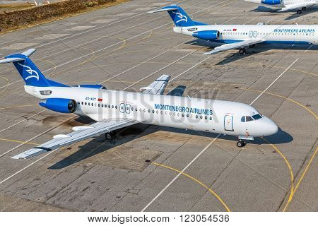 PODGORICA, MONTENEGRO - AUGUST 11, 2015: Aerial view of the Montenegro airlines airplanes Fokker 100 at the airport parked on the runway.