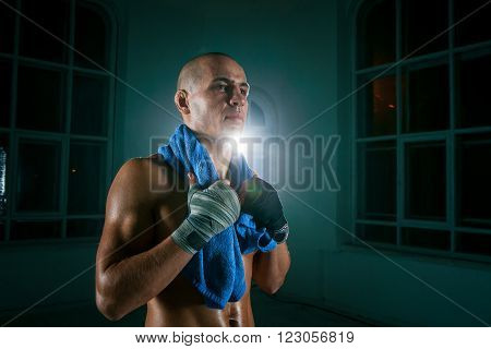 The young male athlete kickboxing on a black background with a towel after a workout drinking water