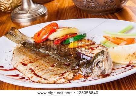 Trout with grilled vegetables on white plate