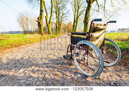 Empty wheelchair on the field road at sunset. Miracle concept. Healed person raised and went away