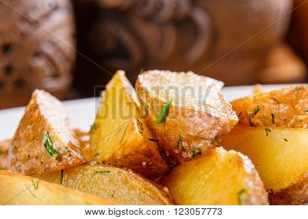 Fried potato wedges with herbs on white plate