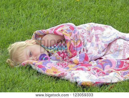 Sleepy little blond girl with pacifier and wrapped in a colorful towel. ** Note: Visible grain at 100%, best at smaller sizes