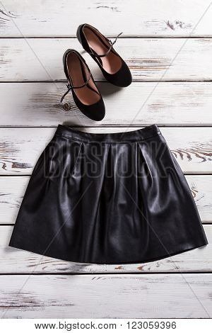 Suede heel shoes and skirt. Woman's dark shoes on shelf. Expensive clothes in city shop. Nice apparel for young women.