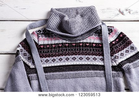Woman's pullover with small ornament. Gray pullover on white table. Piece of clothing with ornament. Trendy sweater with folded collar.