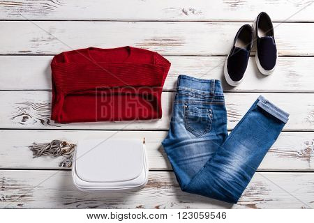 Lady's red sweatshirt and jeans. Female clothing on wooden background. Choice of spring casual clothes. New collection in outlet shop.
