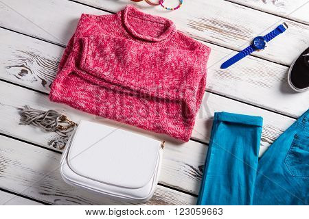 Pink sweater and white handbag. Clothing and accessories on display. Spring sale at huge discounts. New clothes for fair price.