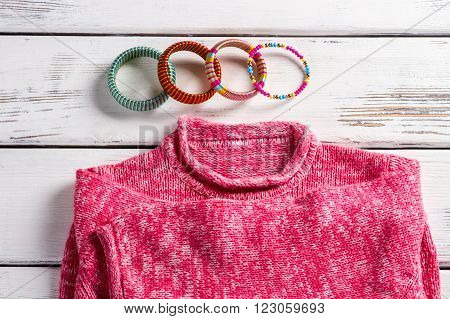 Pink wool pullover and bracelets. Bright pullover on store showcase. Close-up of bracelets and sweater. High-quality clothes in magazine.