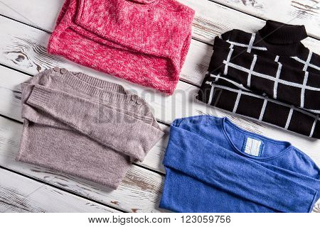 Set of different female pullovers. Few pullovers laying on showcase. Clothing of different pattern. Merchandise from fresh catalog.