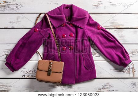 Purple coat and beige handbag. Coat and purse on showcase. New merchandise at fashion house. Wooden showcase with stylish garment.